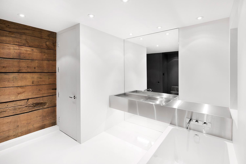 Prosta łazienka z drewnem i stalowym zlewem