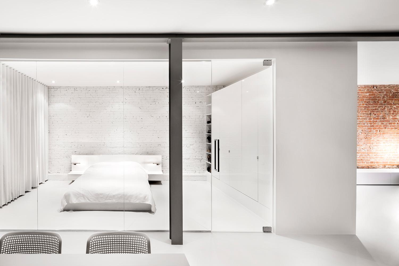 Biała sypialnia za szklaną ścianą