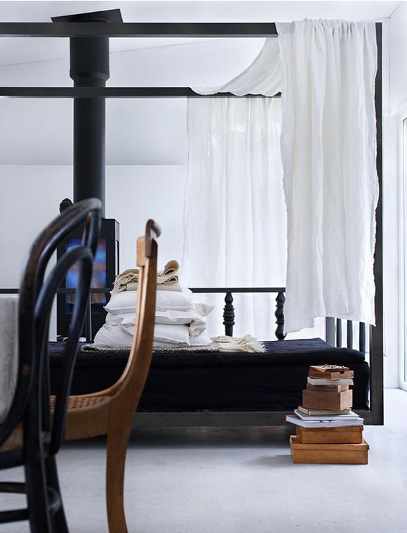 Biała sypialnia z czarnym łóżkiem