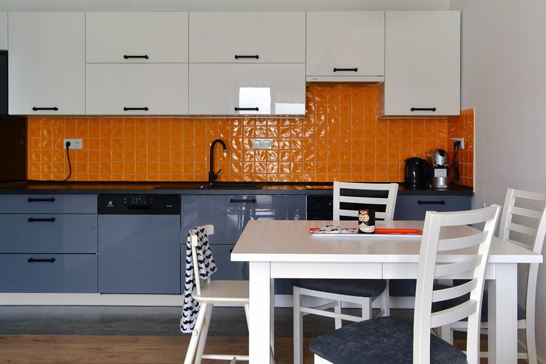 Kuchnia z pomarańczowymi płytkami i białym stołem kuchennym