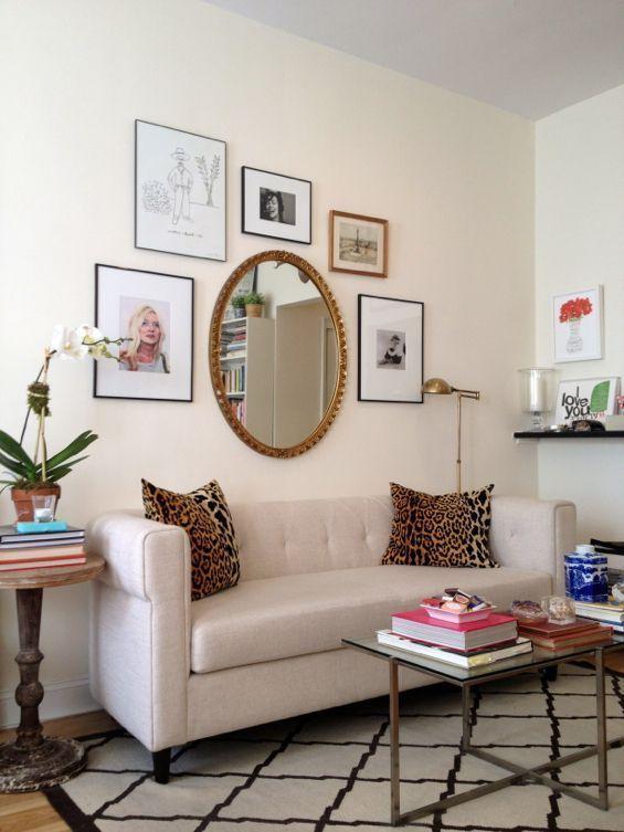 złote lustro i fotografie nad białą sofą