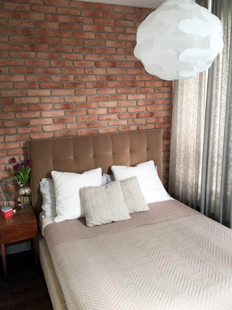 Sypialnia z czerwoną cegłą na ścianie i tapicerowanym beżowym łóżkiem