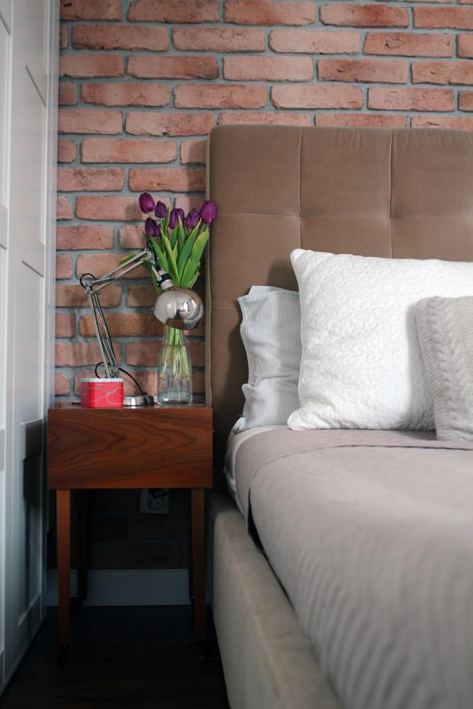 Pikowane, tapicerowane łóżko i drewniana szafka nocna